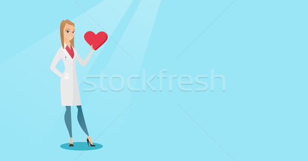 Doctor cardiologist holding heart. Stock photo © RAStudio