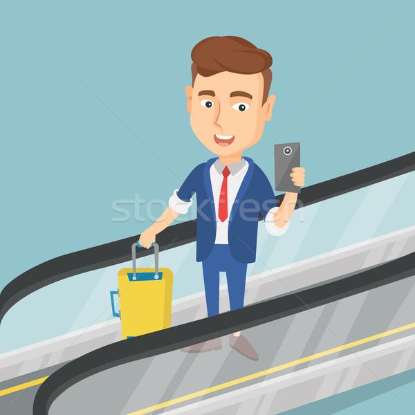 Homme smartphone escalator aéroport jeunes Photo stock © RAStudio