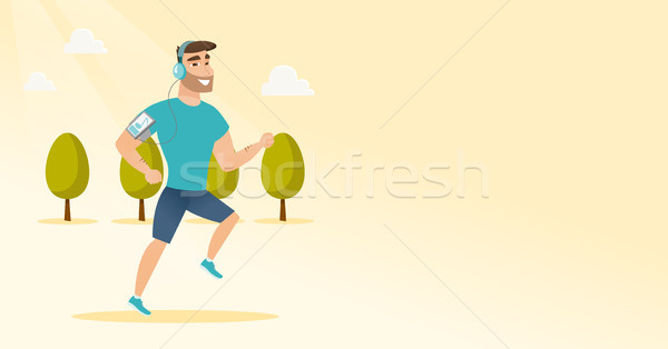 Stock photo: Young man running with earphones and smartphone.
