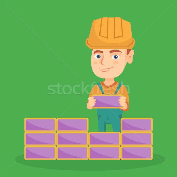 Caucasian bricklayer boy building a brick wall. Stock photo © RAStudio