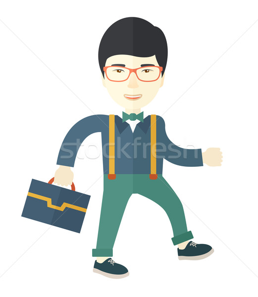 Young asian man walking with his briefcase. Stock photo © RAStudio