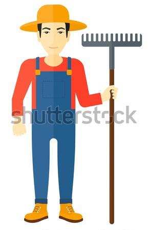 Woman standing with rake. Stock photo © RAStudio