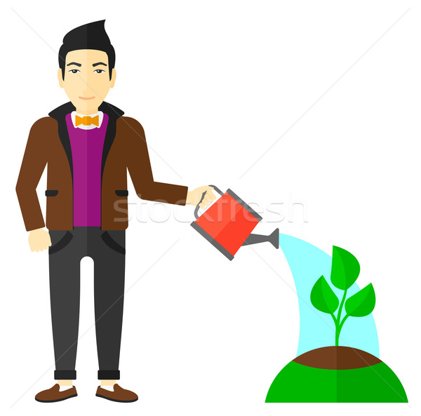 Stock photo: Man watering tree.
