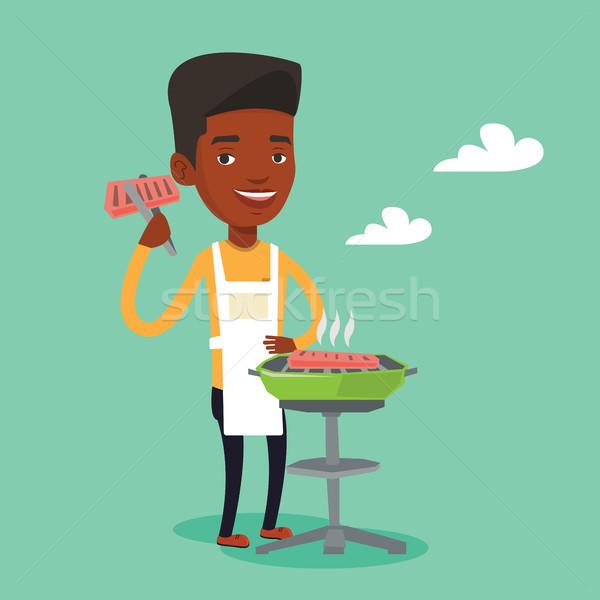 Férfi főzés steak barbecue grill fiatal mosolyog Stock fotó © RAStudio