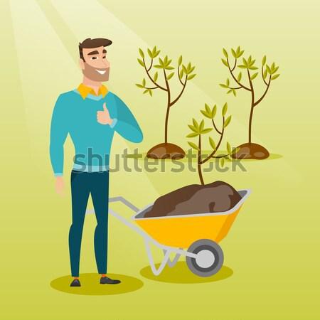 Homme poussant brouette usine jardinier saleté Photo stock © RAStudio