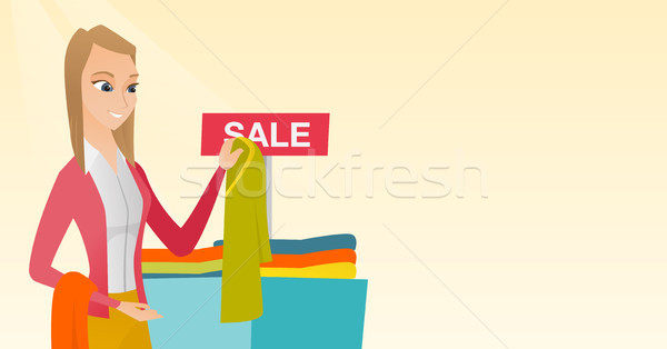 Young woman choosing clothes in the shop on sale. Stock photo © RAStudio