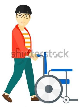 Woman pushing wheelchair. Stock photo © RAStudio