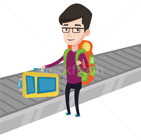 Man picking up suitcase on luggage conveyor belt. Stock photo © RAStudio
