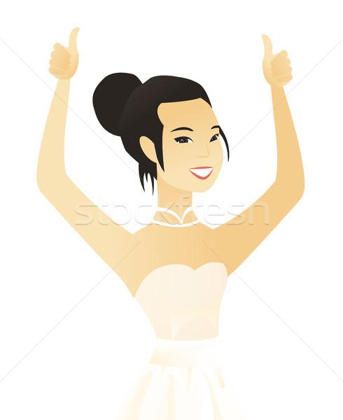 Young asian fiancee giving thumb up. Stock photo © RAStudio