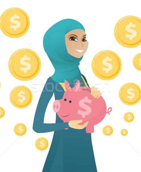 Young muslim business woman holding a piggy bank. Stock photo © RAStudio