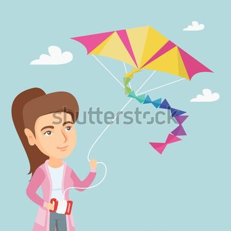 Young african-american woman flying kite. Stock photo © RAStudio