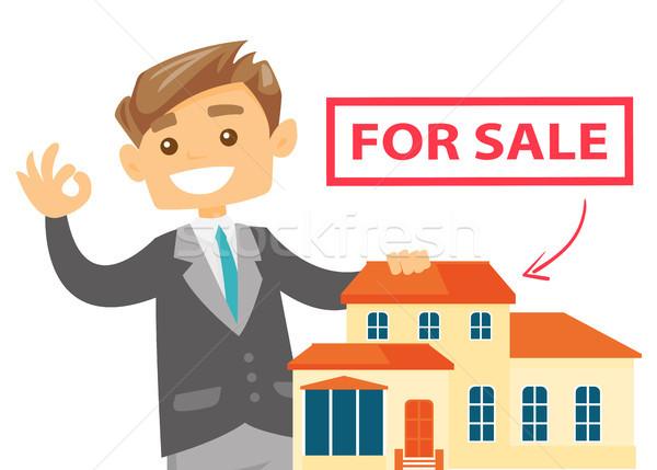 Agent immobilier offrant maison jeunes blanche Photo stock © RAStudio