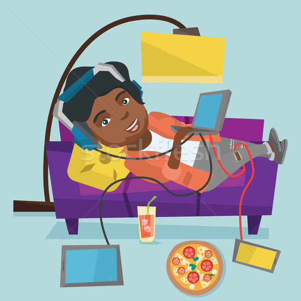 African fat woman lying on sofa with gadgets. Stock photo © RAStudio