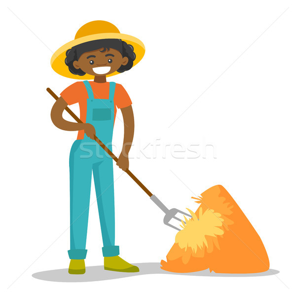 A black happy woman with a pitchfork and a haystack. Stock photo © RAStudio