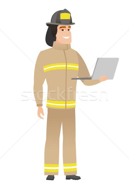 Brandweerman met behulp van laptop kaukasisch uniform jonge Stockfoto © RAStudio