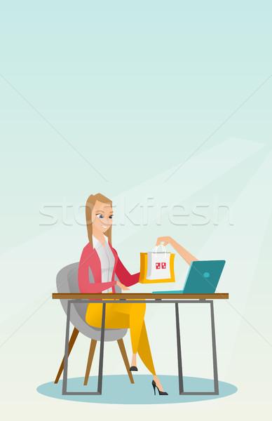 Caucasian woman getting shopping bags from laptop. Stock photo © RAStudio