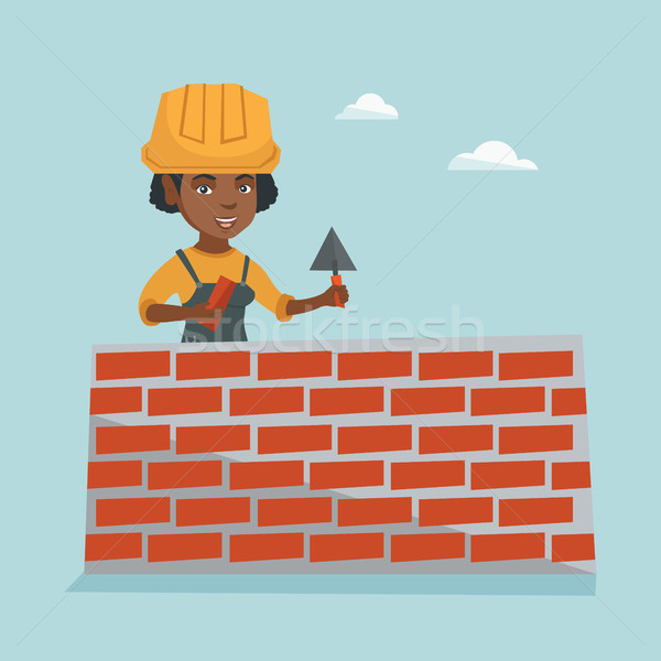 Young african bricklayer building a brick wall. Stock photo © RAStudio