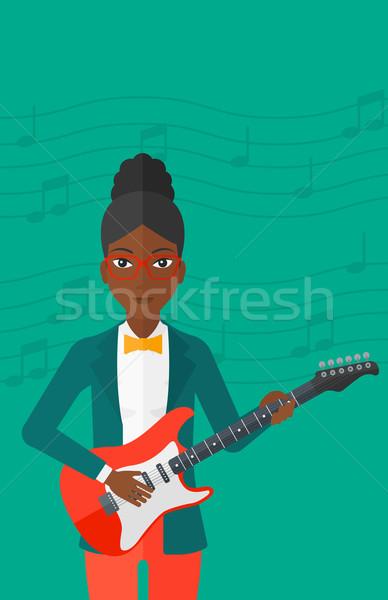Musicista giocare chitarra elettrica donna verde chiaro note musicali Foto d'archivio © RAStudio