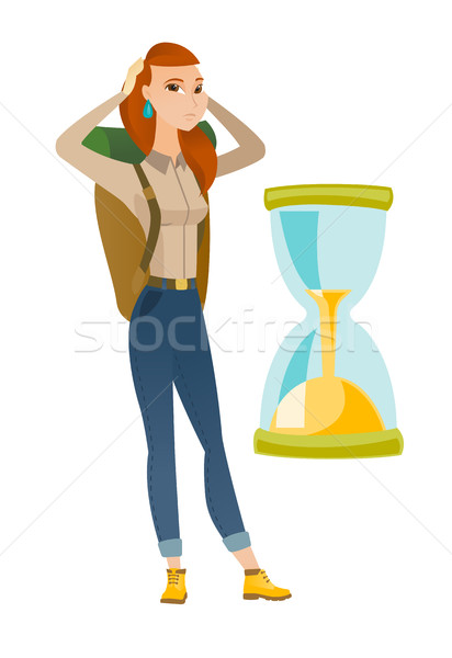 Caucasian traveler woman looking at hourglass. Stock photo © RAStudio