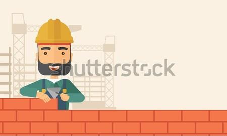 Young bricklayer working with spatula and brick. Stock photo © RAStudio