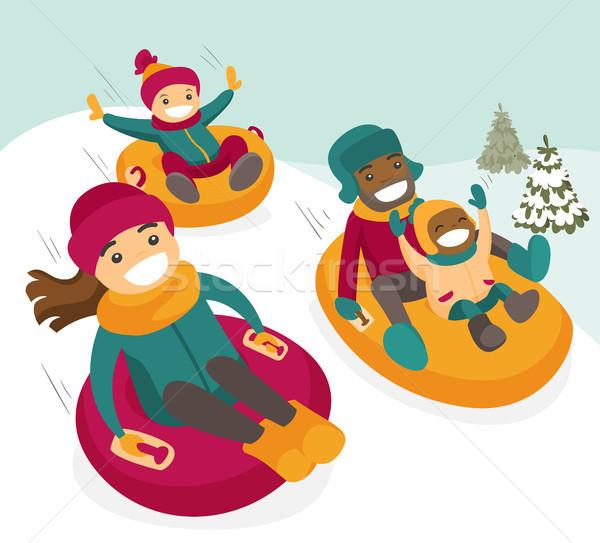 Multiethnic family sliding down the hill on tubes. Stock photo © RAStudio