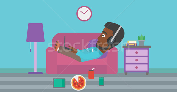 Man lying on sofa with many gadgets. Stock photo © RAStudio