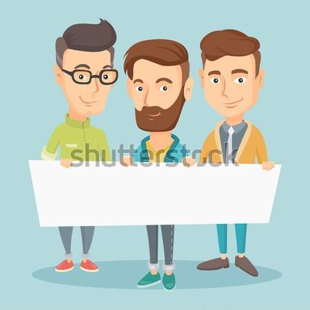 Group of young men holding white blank board. Stock photo © RAStudio