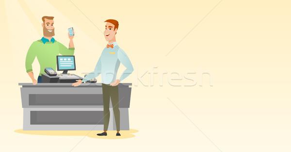Férfi fizet drótnélküli okostelefon fiatal kaukázusi Stock fotó © RAStudio