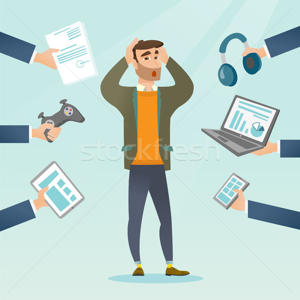 Young caucasian man surrounded by his gadgets. Stock photo © RAStudio