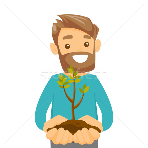 Caucasian white man holding green plant in soil. Stock photo © RAStudio