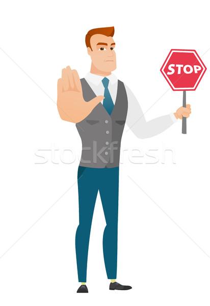 Caucasian businessman holding stop road sign. Stock photo © RAStudio