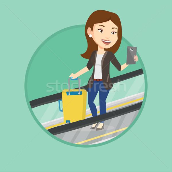 Femme smartphone escalator aéroport femme d'affaires permanent Photo stock © RAStudio