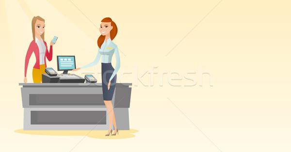 Woman paying wireless with a smartphone. Stock photo © RAStudio