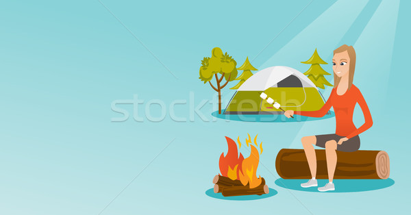 Caucasian girl roasting marshmallow over campfire. Stock photo © RAStudio