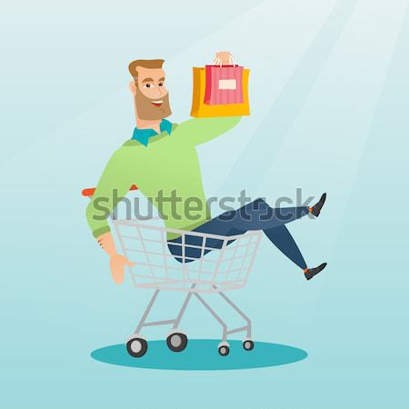 Happy man riding by shopping trolley. Stock photo © RAStudio