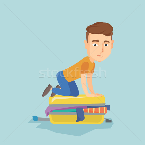 Young man trying to close suitcase. Stock photo © RAStudio