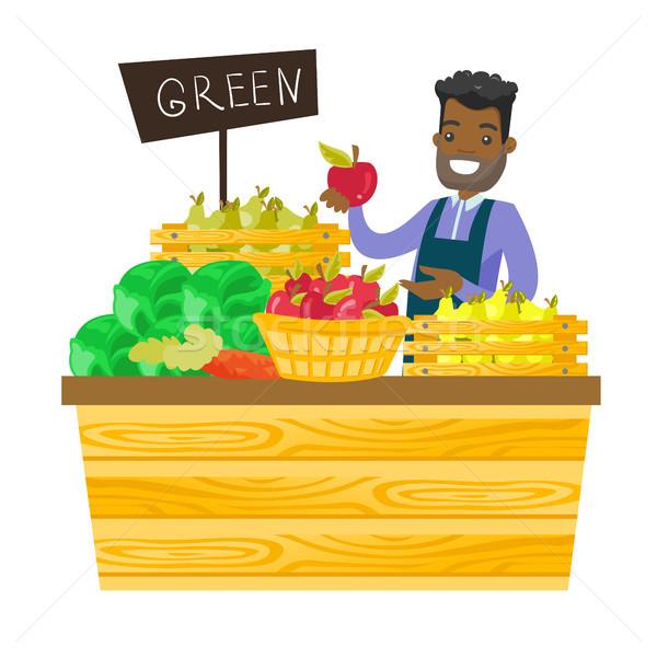 Fiatal munkás élelmiszerbolt áll részleg zöldségek Stock fotó © RAStudio