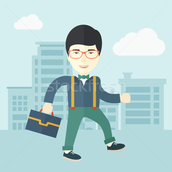 Young man walking through the city street with his briefcase. Stock photo © RAStudio