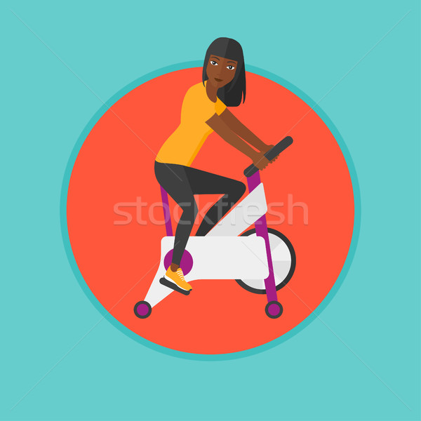 Woman riding stationary bicycle. Stock photo © RAStudio