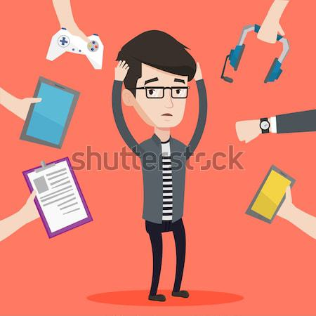 Young man surrounded with his gadgets. Stock photo © RAStudio