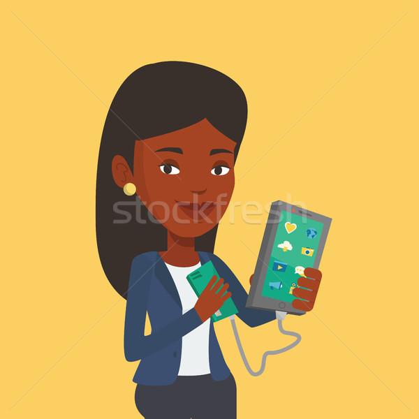 Vrouw smartphone draagbaar batterij glimlachend mobiele telefoon Stockfoto © RAStudio