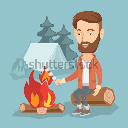 Young man roasting marshmallow over campfire. Stock photo © RAStudio