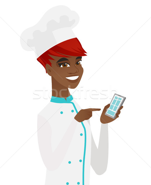 Young african-american chef holding mobile phone. Stock photo © RAStudio