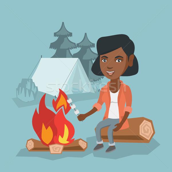 African girl roasting marshmallow over campfire. Stock photo © RAStudio