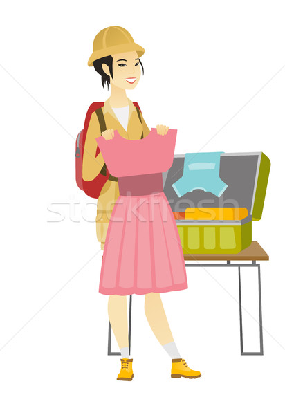 Asian traveler woman packing suitcase. Stock photo © RAStudio