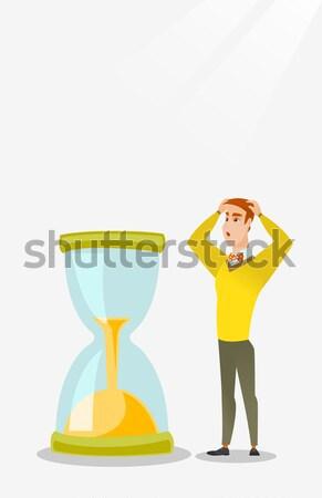 Desperate business woman looking at hourglass. Stock photo © RAStudio