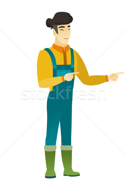 Young asian farmer pointing to the side. Stock photo © RAStudio