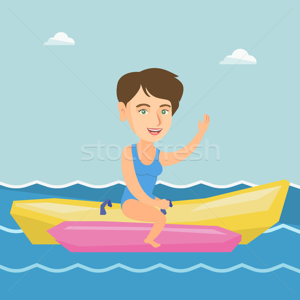 Young happy caucasian woman riding a banana boat. Stock photo © RAStudio