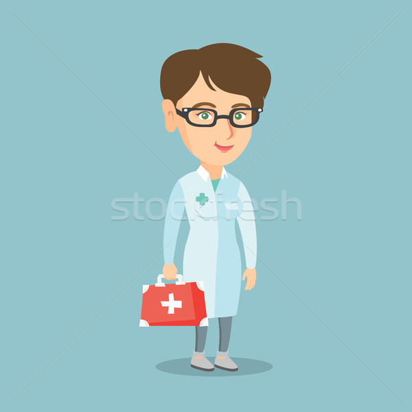 Young caucasian doctor holding a first aid box. Stock photo © RAStudio