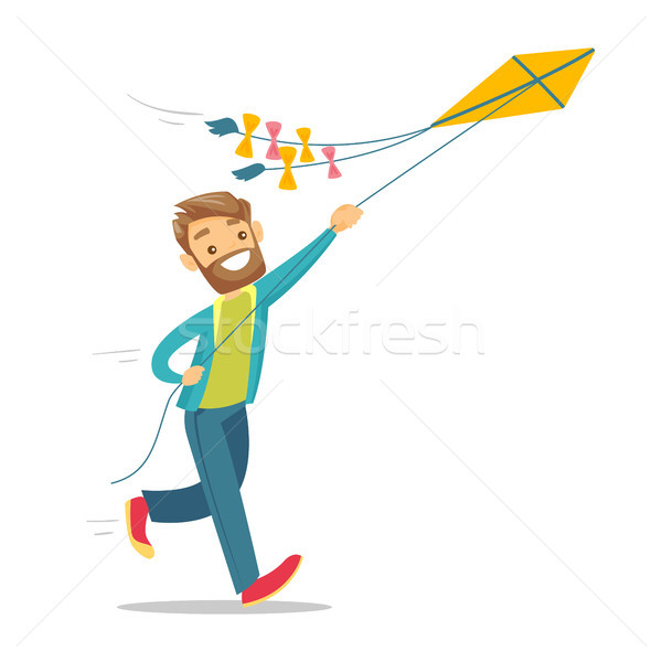 Young caucasian white man flying a kite. Stock photo © RAStudio